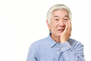 older man with toothache needs to visit emergency dentist